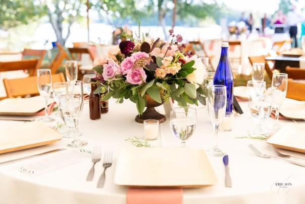 PS Events table setting with floral centerpiece, champagne glasses and blue Saratoga Water bottle.