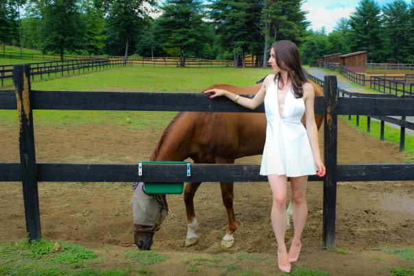 Vlogger Sarah Funky in white dress with horse in Saratoga Springs, NY