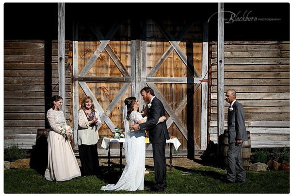 Couple and small wedding party during wedding ceremony in front of barn