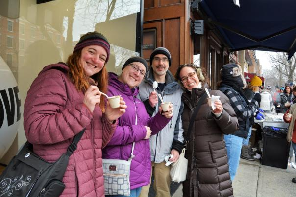 Four people on the sidewalk holding up their cups of chowder and smiling