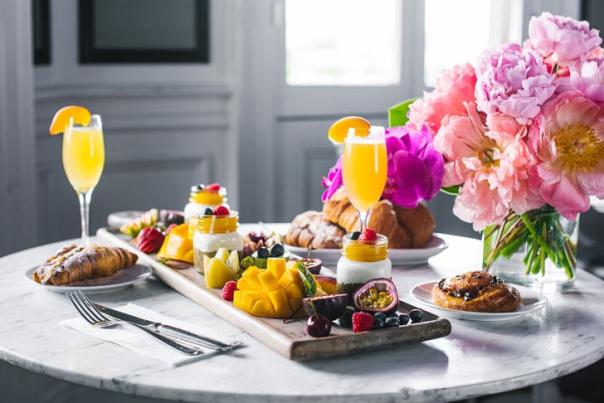 Two mimosas, pastries and fruit with a bouquet of pink flowers from The Blue Hen in Saratoga Springs