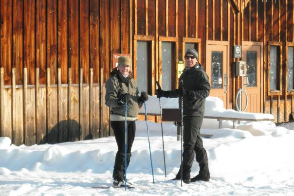 Two skiers standing in front of warming hut at Saratoga State Park