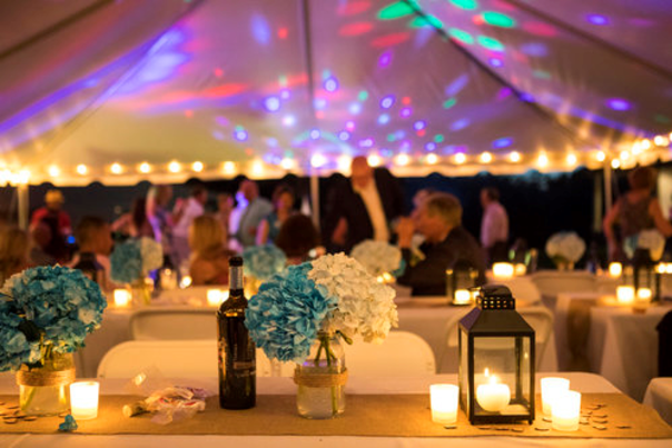 Swedish Hill Farm Evening wedding reception under lit tent with flowers and lanterns