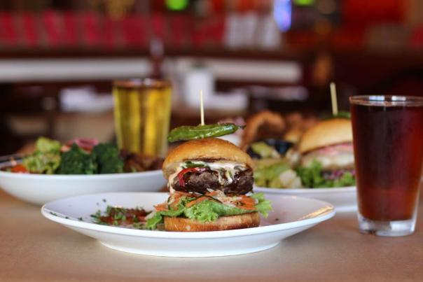 Burger on plate surrounded by beer in glasses