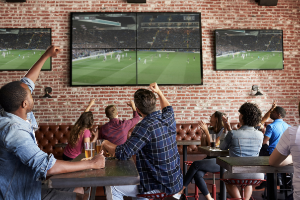 People watching a game while drinking and eating