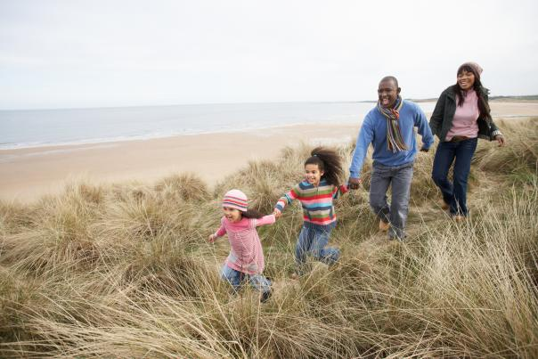 Family running on the dunes by the beach