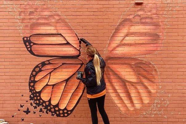Andrea Ehrhardt painting monarch butterfly mural in Springfield Missouri