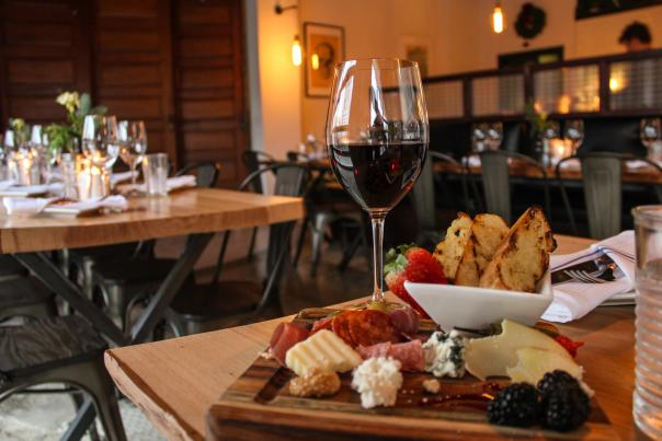 Glass of wine surrounded by charcuterie board