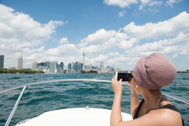 A person takes a photo of the Toronto skyline from a boat on Lake Ontario