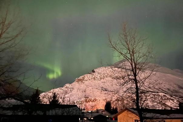 northern lights over mountains and a small Alaskan town