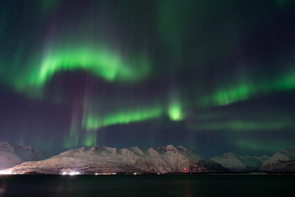 Northern lights over a snow covered mountain, town, and port