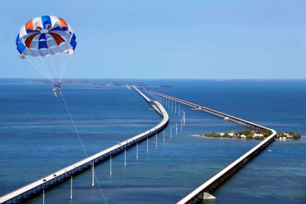 two people parasailing over 7 mile bridge
