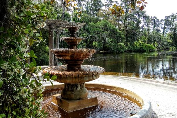 Surrounded by star Jasmine, a water fountain trickles next to a pond at Airlie Gardens