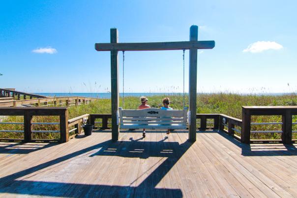 Two People On Boardwalk Beach Swings In Carolina Beach, NC