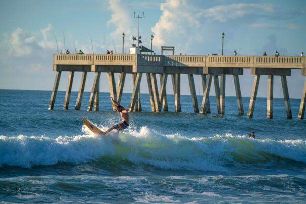Surfer riding a wave by The Pier in Wrightsville Beach