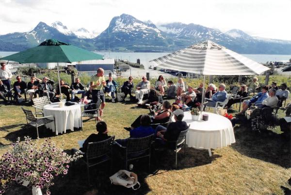 People gathered outdoors for a theatre conference. Mountains and ocean in the background.