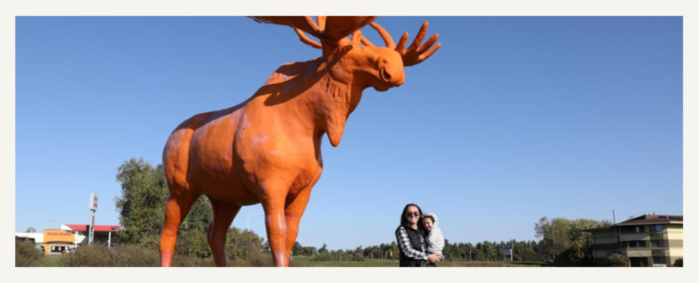 Woman And Child Standing By Orange Moose in Black River Falls, WI