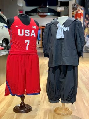 A women's basketball uniform from 2020 sits on display next to a uniform from the 1920s.