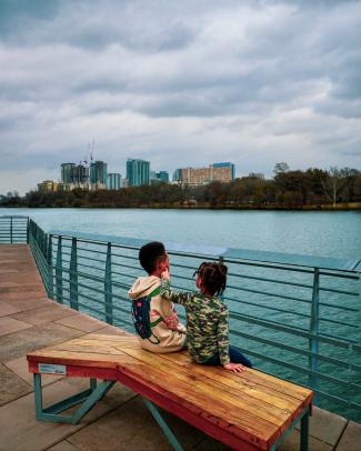 Two young children sitting on a bench on the Hike & Bike Trail Boardwalk. Lady Bird Lake and the Austin skyline are behind them