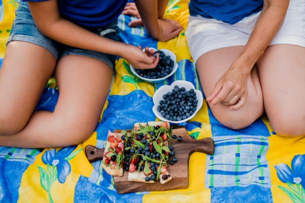 two people enjoying berries and picnic