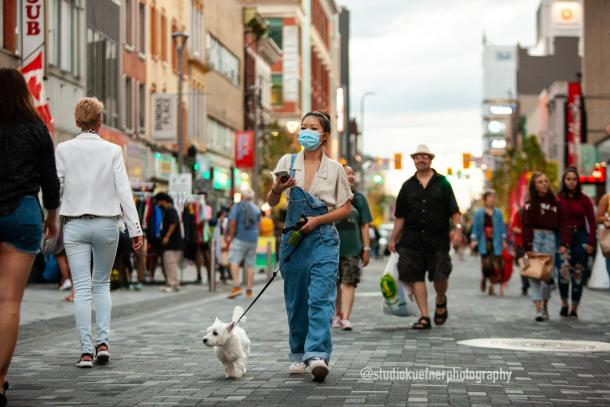 Woman walking dog in mask