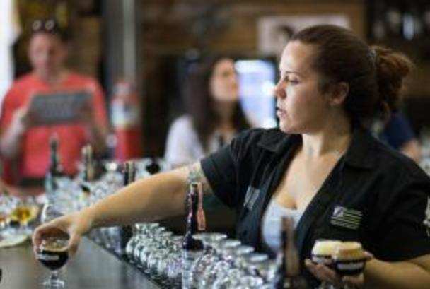 Bartender serving drinks at Adroit Theory Brewing Company