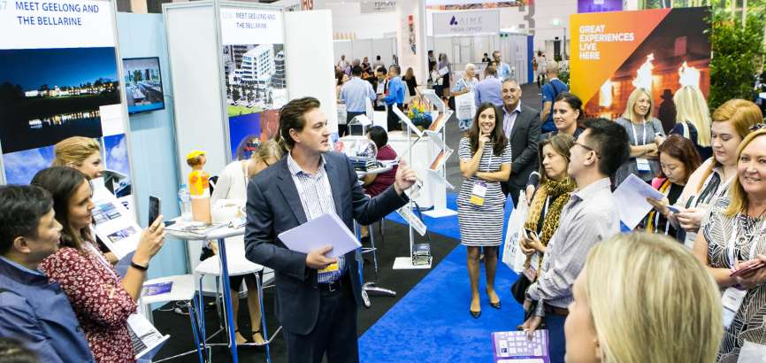 People gathered around a man promoting Regional Victoria at the AIME trade-show