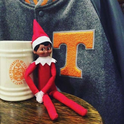 Elf on the Shelf sitting next to a University of Tennessee mug and jacket