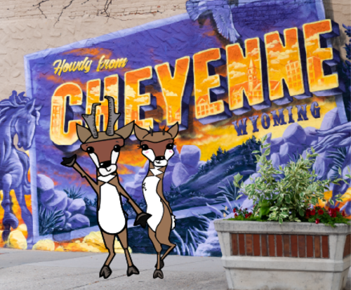 """Two illustrated pronghorn antelope stand in front of the """"Howdy from Cheyenne"""" mural in downtown Cheyenne."""