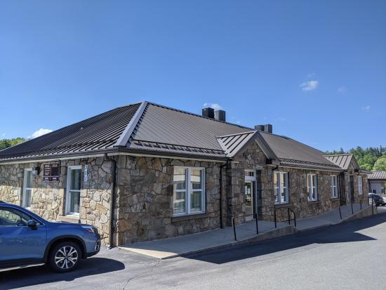 A gray stone building, the Watauga County Courthouse Annex Building, with a row of windows and a door facing the parking lot. A blue car is visible on the left side of the photo.