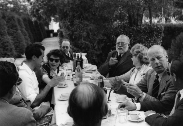 A dinner party in Spain with guests around a table outside. Guests include Ava Gardner, Luis Dominguin and Ernest Hemingway