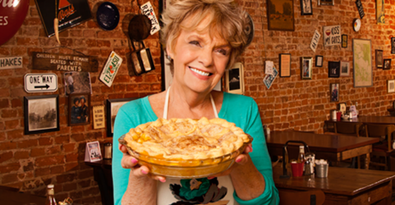 A woman offers up a fresh-baked pie at Maxine's Café & Bakery in Bastrop, TX.