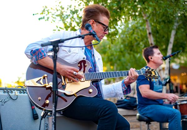 A guitarist performs on an outdoor stage during the Summer Faire Concert Series at Arbor Lakes