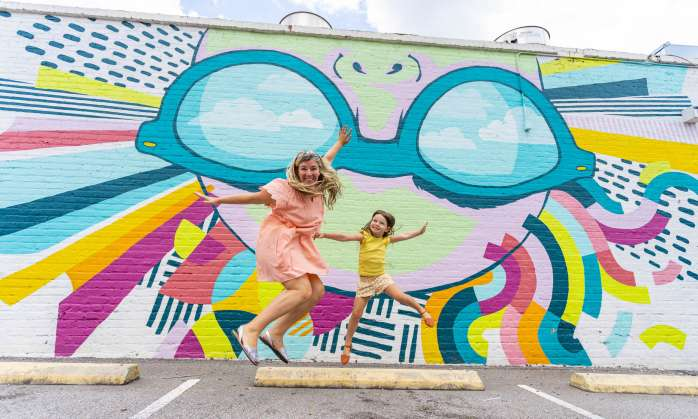 Mother and daughter jumping in front of a mural