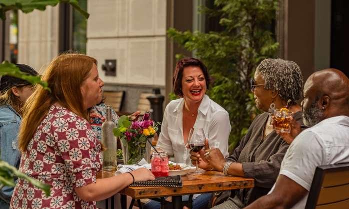 Friends enjoying drinks and dinner outside of Bourbon