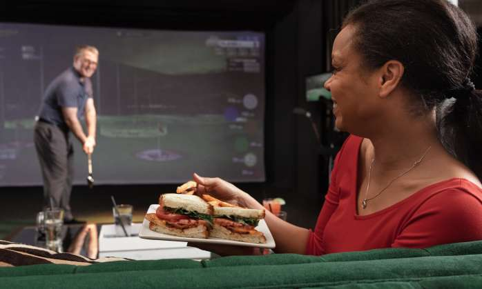 Woman enjoys sandwich while watching her husband play a virtual game of golf at the Main Course
