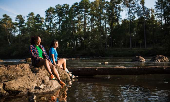 Two women sitting on the bank of the Saluda River