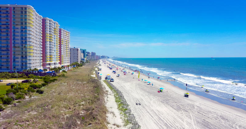 Aerial view of Atlantic Beach coastline with condos on the left and the sandy beach and ocean on the right