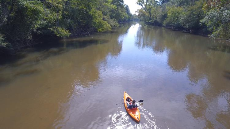 A kayaker paddles a river in the sun captured by a drone.