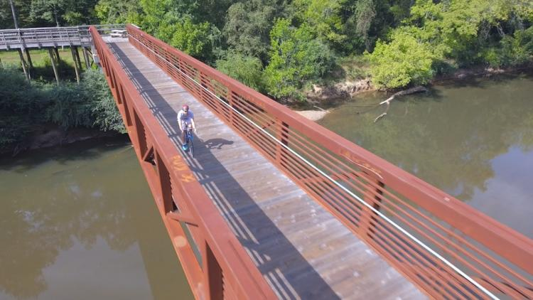Drone Shot of Man Cycling on a Bridge Over a River