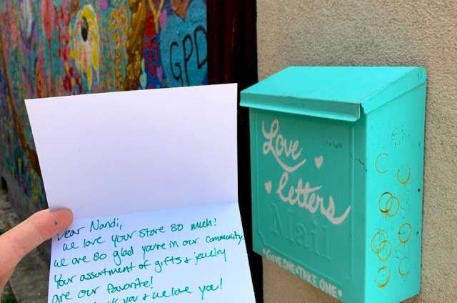 Letter on card with teal blue mail box behind