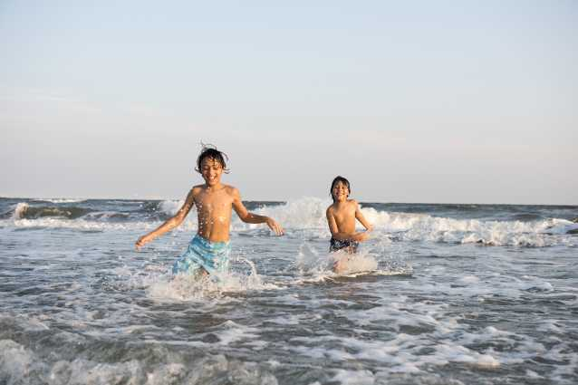 Boys playing in the surf at family friendly beach