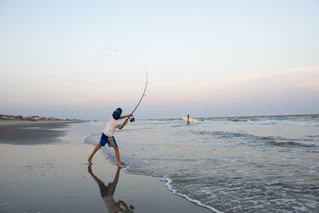 Boy surf fishing on Ocean Isle Beach