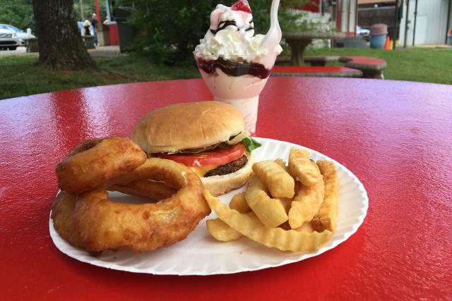 A local joint serves up a cheeseburger with onion rings & crinkle-cut fries and an ice cream sundae.
