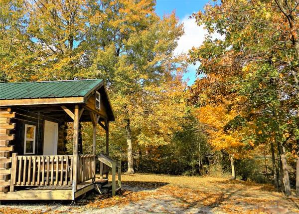 Autumn leaves begin to fall around a cabin at Deam Lake State Recreation Area.