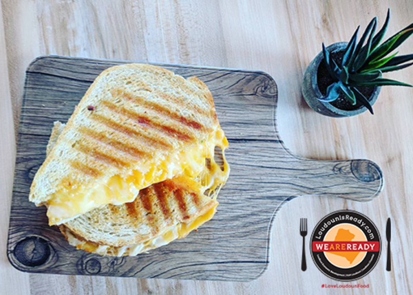 Grilled cheese sandwich on cutting board with LoudounIsReady icon and #LoveLoudounFood