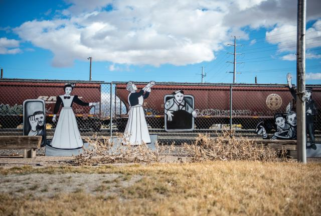Cutouts of Harvey Girls and railroad life decorate a fence outside the Harvey House Museum.