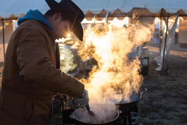 Dawn breaks as a contestant stirs his carne adovada.