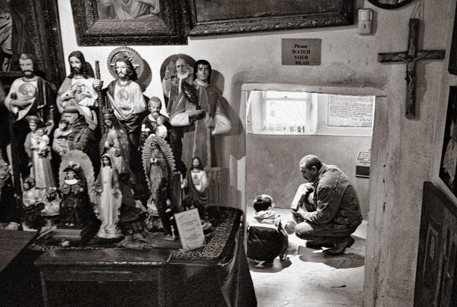 A man and boy kneel to collect healing dirt inside El Santuario de Chimayo