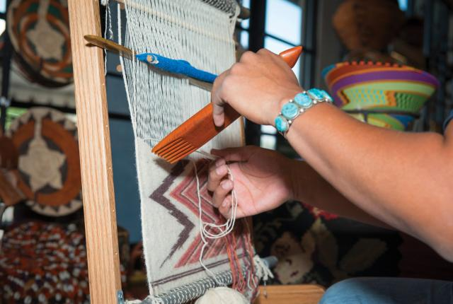 A weaver weaving on a vertical loom at the New Mexico Fiber Crawl